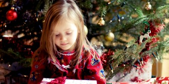 A sweet young girl holding a Christmas present